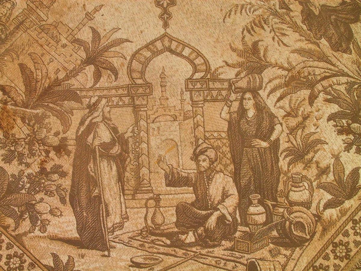 Maurisk rosett/ palmettaktige  blad. ,to  menn og en kvinne utenfor byport, teppe på marken med krukker byport, kvinne foran den, palmer, minareter  etc.