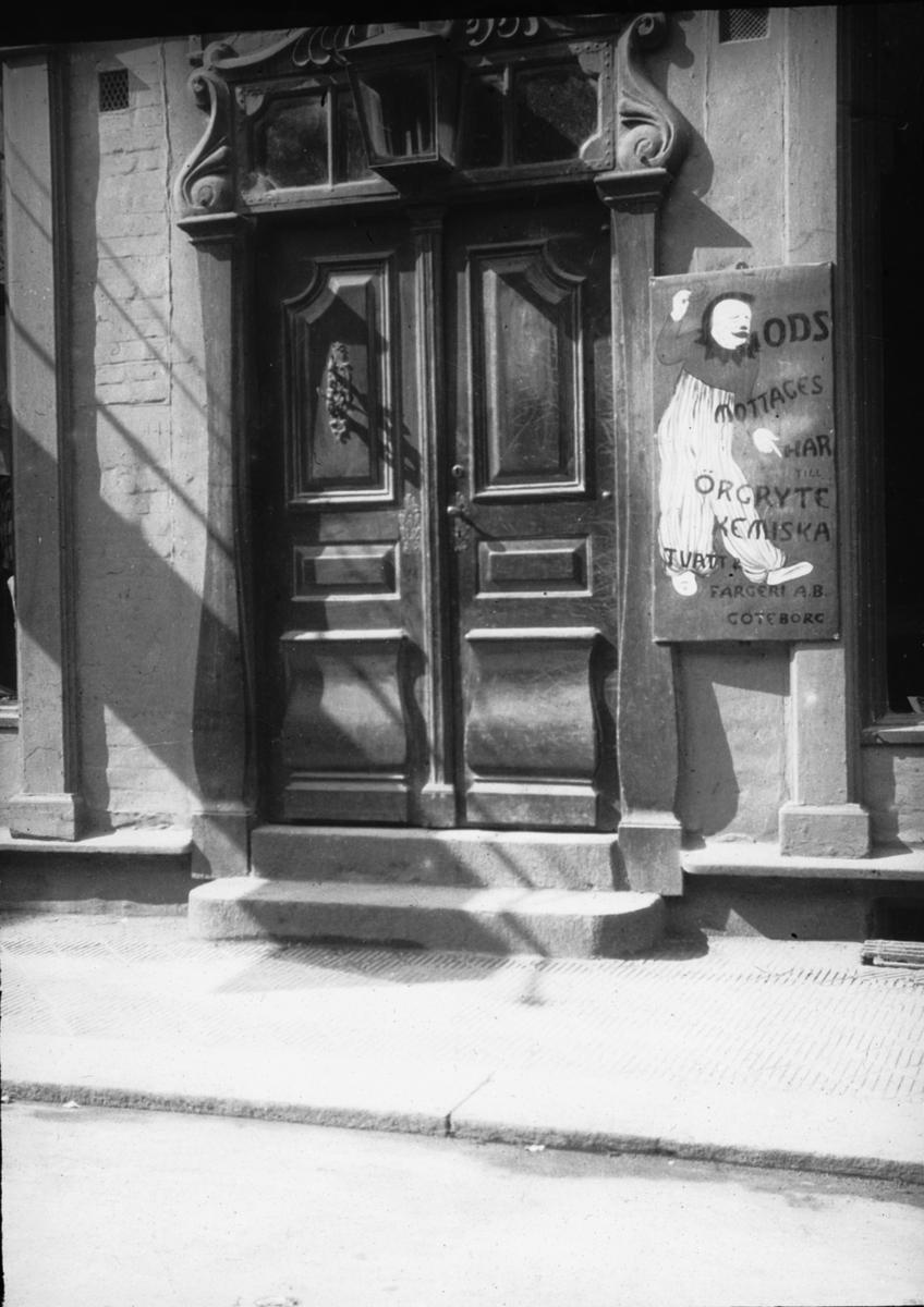 Skioptikonbild med motiv från gata i Helsingborg. Port till godsmottagning, Örgryte Kemiska tvätt och färgeri AB. Norra Storgatan 9 i Helsingborg. Bilden har förvarats i kartong märkt: Helsingborg 8. 1908.