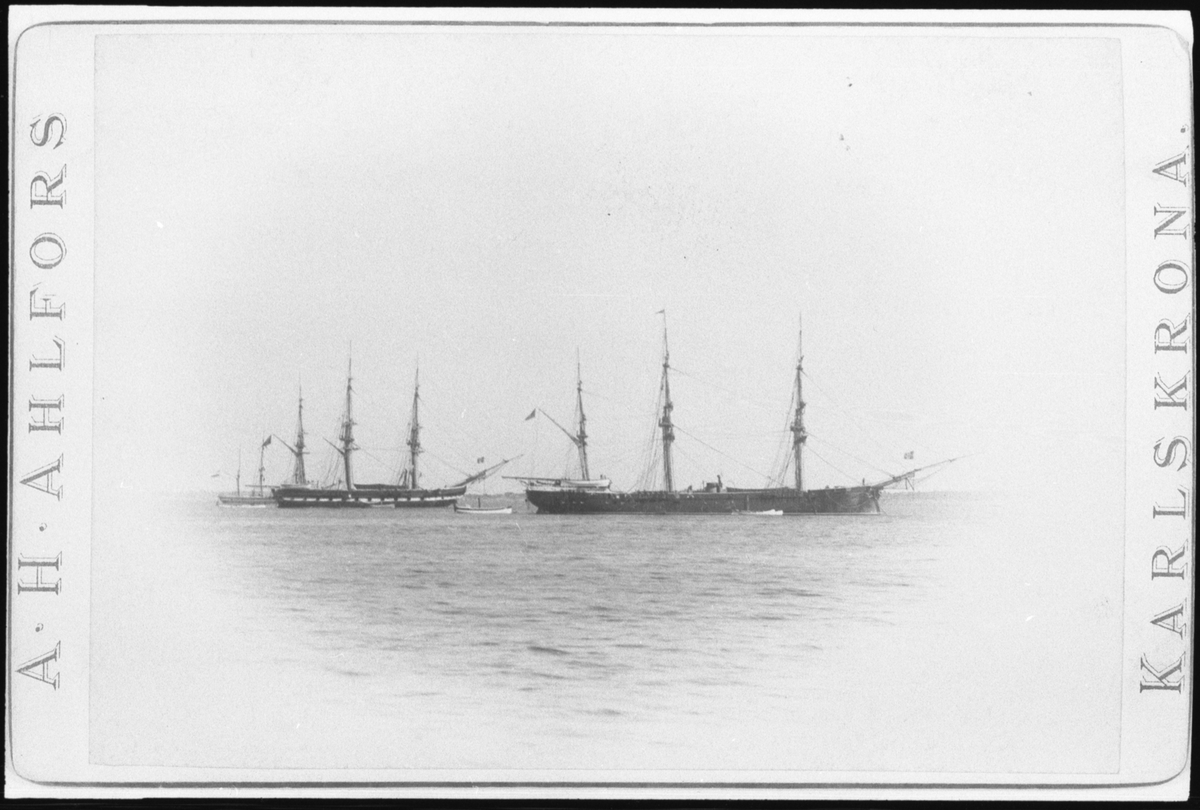 Reprofotografi efter ett vykort som visar fregatten Norrköping och korvetten Saga som ankrar i Karlskrona. Vänster om Norrköping ligger en tredje segelfartyg. Före skeppen syns flera mindre roddbåtar.