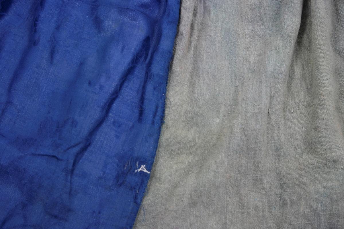 Capet består av 4 hoveddeler og 2 splitt-stykker i hver side. Påsydd rødt bånd/stropp i høyre side innvendig. Folder rundt halsen, jevnt fordelt i ulike bredder. Sydd ned med attersting som ser ut som prikkesting på rettsiden. Foret med grovt linstoff.
