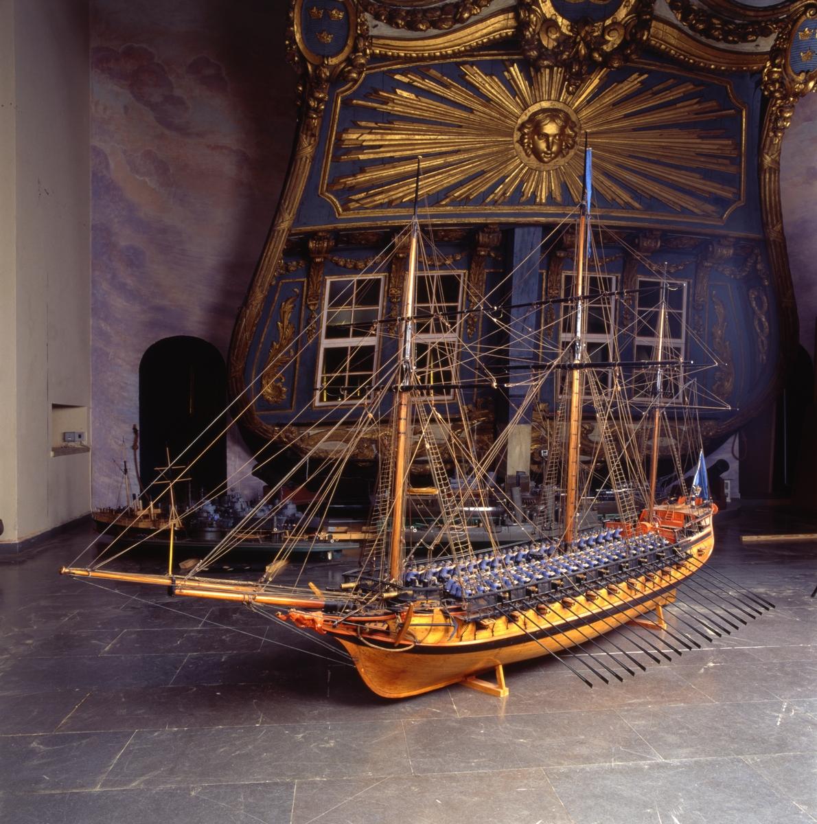 """Fartygsmodell, skärgårdsfregatt, turuma Lodbrok, Chapmans konstruktion. Tremastad, riggad utan segel med blå flagg och vimpel. 19 par årtullar. 20 st åror. 2 st bärlingar. Bordläggning på spant med däcksinredning, skulpterad, rödmålad akterspegel med namnet """"Lodbrok"""" samt kartuscher, en med vasakärve och två med stjärnstrålar. Galjonsfigur, röd. Fernissad med svart och rött berghult. Bastingage svart. Rår och toppar svarta. Däcksbyggnader röda. 52 kanoner av förgyllt trä. Kompletterad och restaurerad."""