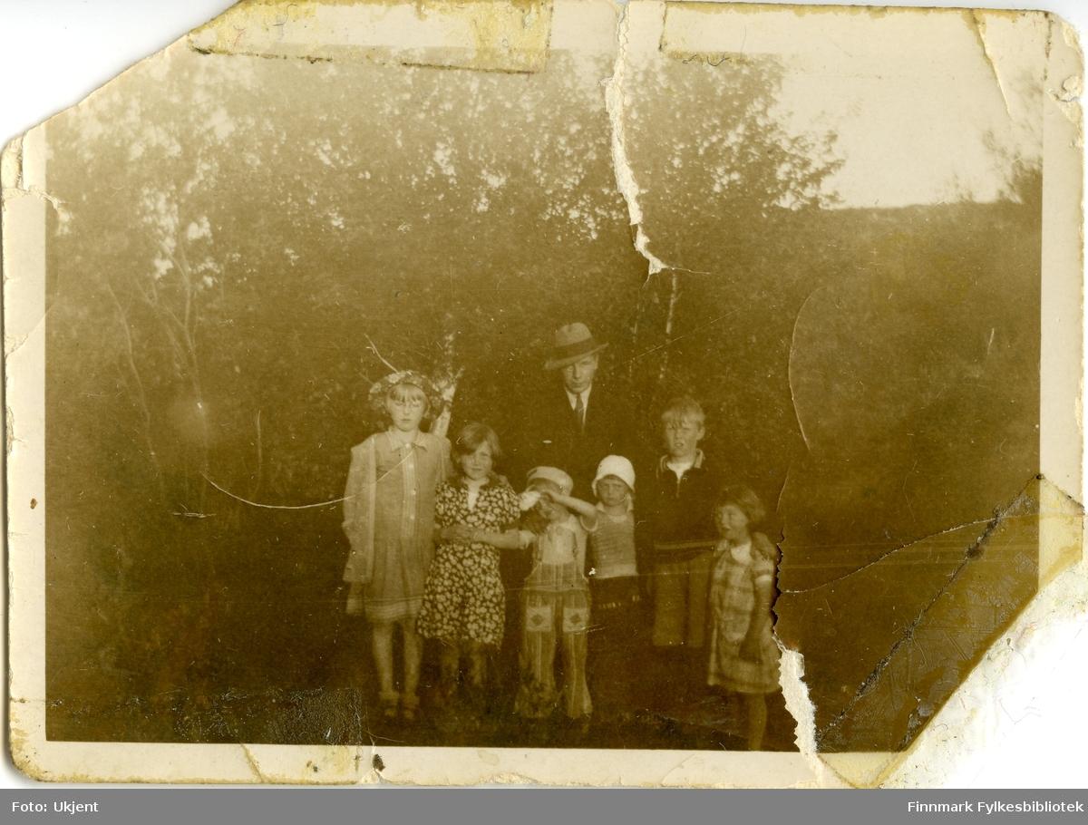 Et gruppeportrett av ukjente barn og voksen. Barna er kledd i kjoler, bukser, hatter, jakker, shorts og sko. Mannen er kledd i dress, slips og hatt.