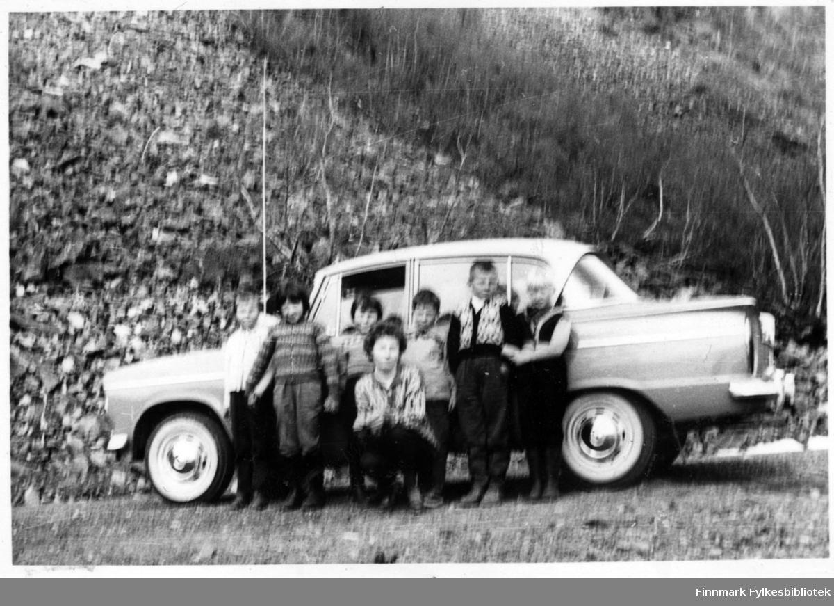 Ragnhild Lorentzen (fotograf) og Irene Martinsen på skoletur på vei til Alta med 2.klassinger ved barneskolen i Nuvsvåg våren 1963. Barna på bildet er fra venstre: Jorunn Kårsgård, Norun Jensen, Asbgjørg Henriksen, Odin Eriksen, Gunnar Olsen og Henning Nilsen. Barna er kledd i bukser, gensere og sko. Enkelte av dem lener seg mot bilen.