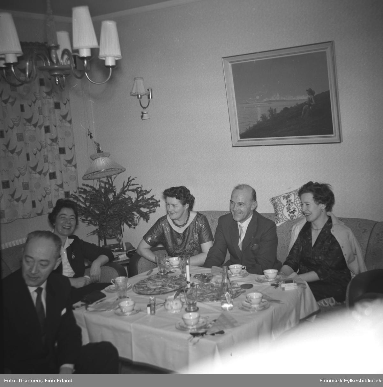 Fem personer sitter rundt bordet hjemme hos familien Drannem i Hammerfest. Jenny Drannem sitter i hjørnet ved siden av potteplanten. De andre personene er ukjent.