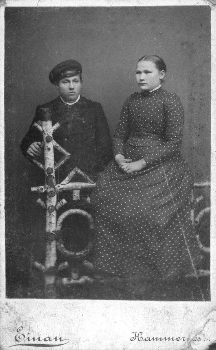 Visittkortportrett av et ungt par. Kvinne sitter på en oppsatt gjerde, mannen står bak.