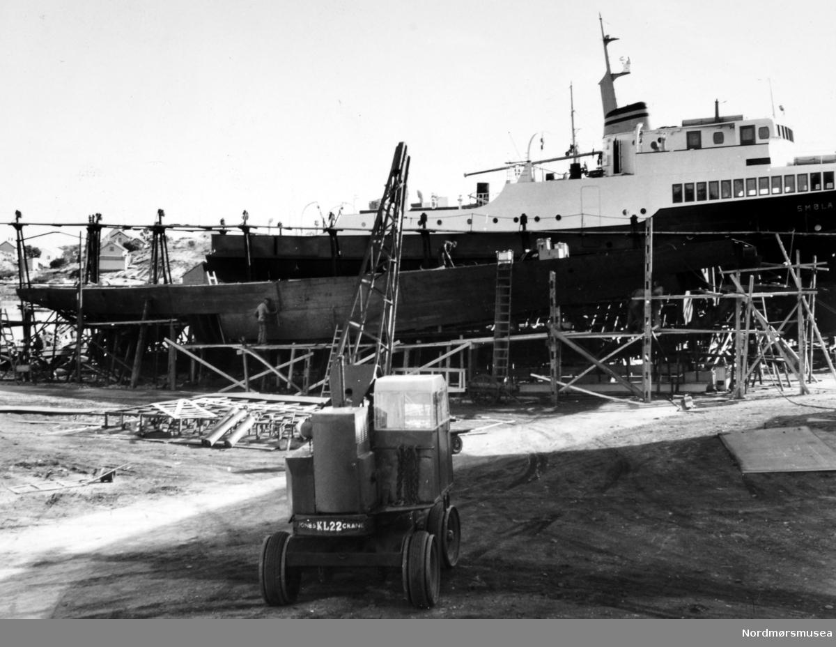 """Bildet viser B/F""""Norddalsfjord"""" Storviks Mek. Verksteds bnr.14 på beddingen under byggingen. Foto KMb-1983-031.0278 og foto KMB-1983-031.0279. Disse fotoene er helt like og med lik tekst. -  """"Norddalsfjord"""" ble levert til Møre og Romsdal Fylkesbåtar 15. mars 1961 og hadde følgende hoveddimensjoner: L 31,20 m x B 8,55 m x D 3,35 m og hadde en tonnasje på 159 bruttoregistertonn. Fremdriftsmaskineriet består av 3 Volvo Penta turboladede dieselmotorer type TMD96 på til sammen 420 hk som via kilremdrift var koblet til et felles gir og propellaksel med vribar propell, slik at hver enkelt av motorene kunne kjøres separat. Fergen hadde 2 Bolinders vekselstrømsaggregater type 1052MG på 23 hk hver tilkoblet en generator på 17 kW. Fergen var utstyrt med elektrohydraulisk styremaskin.  Fergen har plass til 18 personbiler og har sertifikat for 160 passasjerer. Forut er det innredet 6 lugarer for offiserer og restaurantpersonale og akterut en mannskapslugar for 4 personer og toppfarten er 11,4 knop og marsjfarten 10,5 knop.  Ferga er verkstedets første nybygg etter B/F""""Trygge"""" som ble levert i 1938.  På den nye patentslippvogna klinkbygd i stål 1918, den største slippen mellom Bergen og Trondheim, står B/F""""Smøla"""" til MRF. Aktenfor """"Smøla"""" og over nybygget ses fra venstre bolighuset, med uthuset foran, til familien Martinus Olsen, senere familiene Olaf og Alfred Olsen, senere familien Olaf Olsen. Dernest mønet på Essos garasje. Bolighusene til høyre er fra forrest Rikard Rikardsens, familien Iver Kolvik, senere familien Theodor Wang med uthus og over dette ses så vidt Essos bolighus, hvor først familien Kristian Gaupseth bodde, senere familien Olaf Øie, senere familien Thore Wullum.  Under hekken på Smøla ses naustet til Olaf Olsen/Rikard Rikardsen. Under hekken på nybygget skimtes også fiskeskøyta til Olaf Olsen i utlegget.  I forgrunnen ses verkstedets mobilkran av engelsk fabrikat Jones type KL 22 og med en maksimal løfteevne på 2 tonn. Den ble drevet av en 1-sylindret dieselmo"""