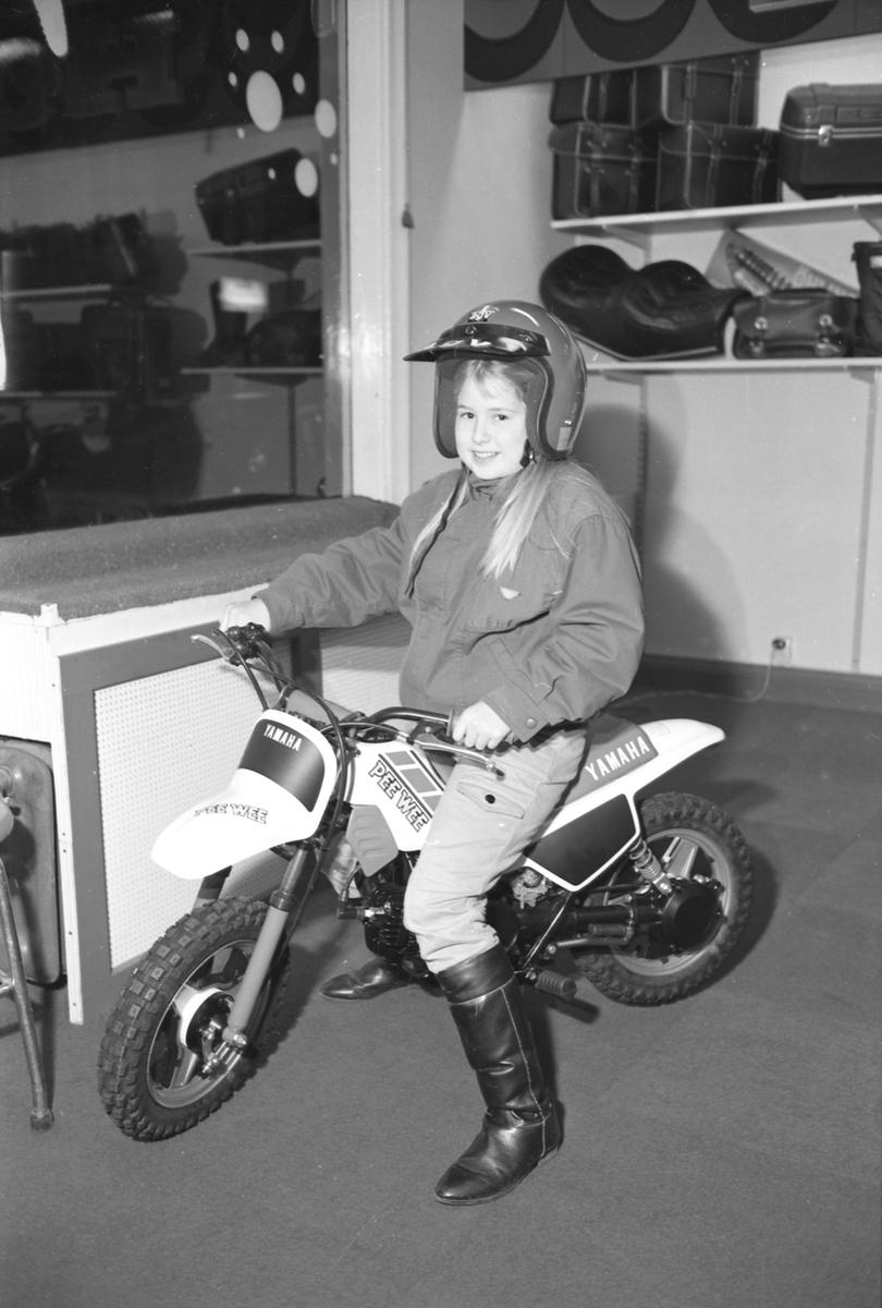 Ung dam vinner minicrosscykel i en tävling anordnad av Team Westom i Arvika. Butiken heter Wachenfeldts Motor på Kyrkogatan 18 och bilden togs i november 1985.