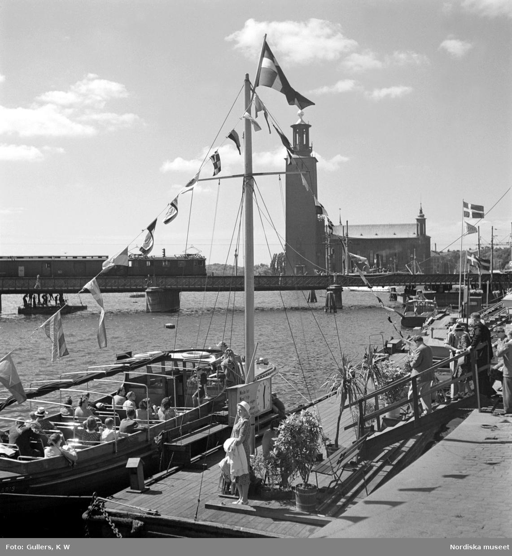 Stockholm. Turistbåtar vid Tegelbacken, Norra järnvägsbron och Stadshuset i bakgrunden.