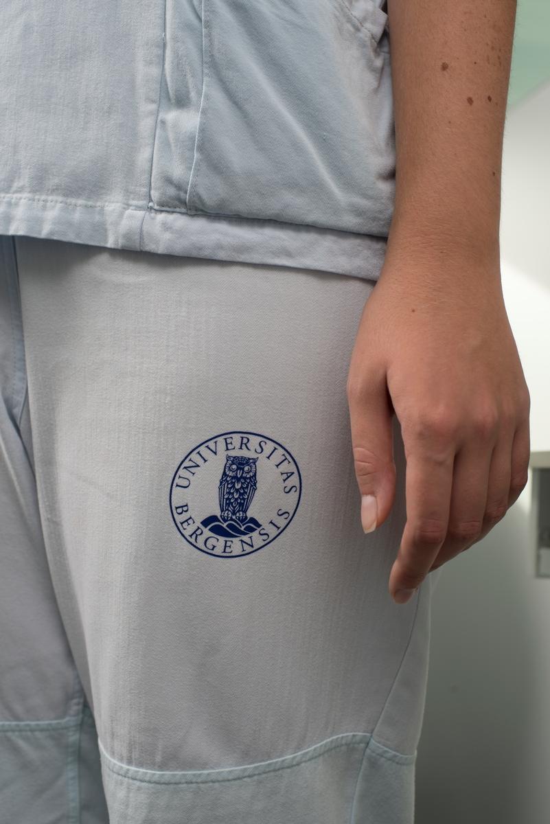 Klær er identitetsskapende. Til de ansatte i tannklinikken har Ida Falck Øien tegnet og produsert tannlegedrakter med nytt snitt og farge. Inspirasjonen til designuttrykket har hun funnet ved besøk i det gamle odontologibygget, fra populærkultur og fra tannlegefagets historie, samt fra egne barndomsminner om tannlegebesøk.  En jevn syklus av tannlegeuniformer brukes, vaskes, strykes, brettes og brukes om igjen dag etter dag. Systemet for klærne er både en konkret bekjempelse av smitte og kaos og en metafor for det hele. Snittet på de nye plaggene er inspirert av dette urverket av et system.