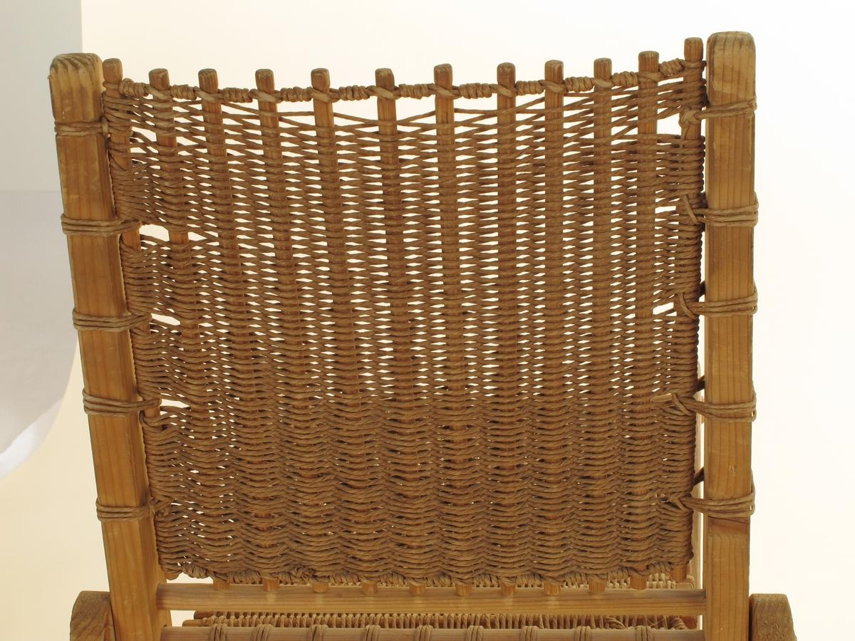 Klappstol med ryggstøtte. Laget av lektebiter av nåletre, trolig gran, rektangulært tverrsnitt i bærende opprettstående elementer, runde spinklere i tverrbjelkene som forbinder disse. Ingen spiker, delene er satt sammen i runde hull og holdt på plass av tynne trenagler. Sete og ryggstøtte er laget av runde pinner som er flettet med papirhyssing. Alt er i naturfarger, ingen maling eller annen overflatebehandling. Et tydelig sekundært trestykke er skrudd fast til den ene ryggstolpen som ekstra støtte og lås. Tilstand: Setets surring til seteforkant er røket på stolens ene side.