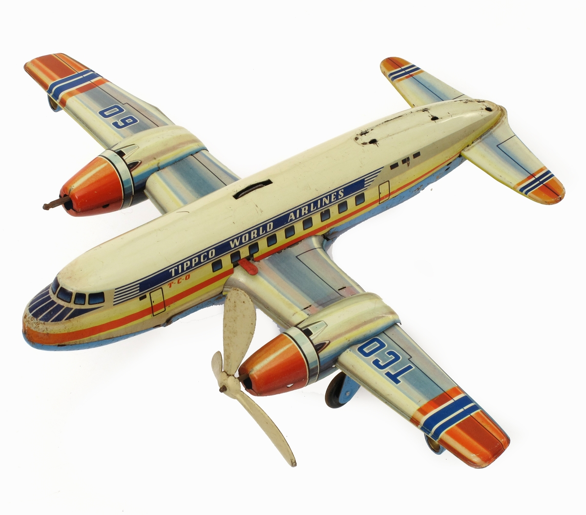 Lekefly, propellfly, passasjerfly, av jernblikk m.m. Med fjærmotor til opptrekking. Malt i blått, orange og gult.