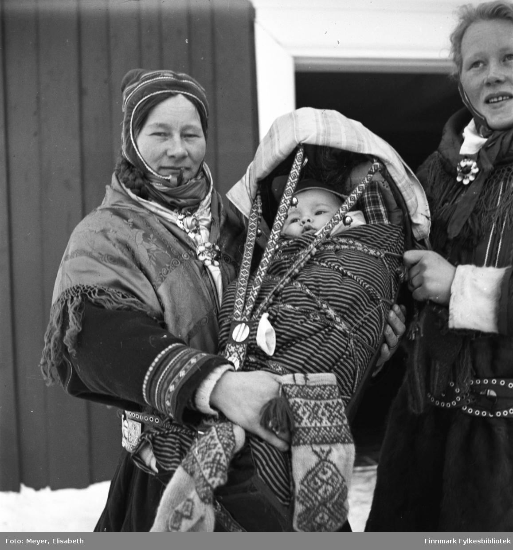 Inga Josefsdatter Buljo med barnet i komse til venstre. Borghild Oskal til høyre i bildet. Fotografert utenfor Kautokeino kirke i perioden 1939-40. Begge bærer samiske kofter og komsa er pyntet. Muligens er dette etter en barndåp. Inga Josefsdatter Buljo holder et par samiske strikkede votter i hånden.