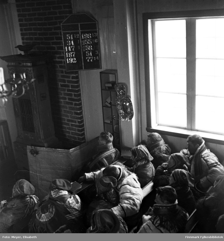 Kirkelig handling fotografert i Kautokeino kirke( 1701-1944) Bildet er tatt  rundt 1939-40. Muligens fra et samisk bryllup eller en samisk dåp. Tavlen med henvisning til salmeboken kan sannsynligvis fortelle noe om det er bryllup eller dåpshandling.
