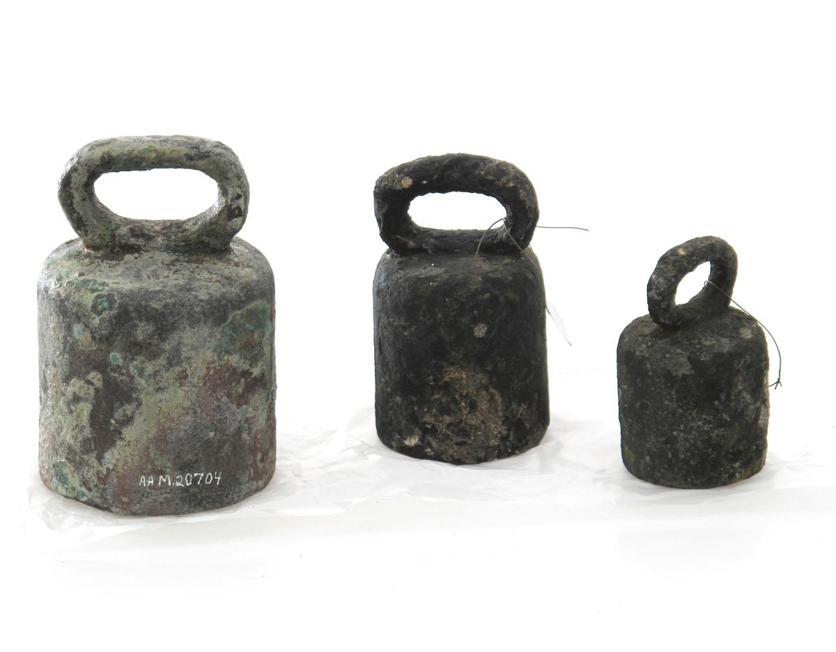 Vektlodd, Christian 5. Av bronse fylt med bly. Sylinderform med bøylehank.  I ovalt felt på den ene frontside i relieff:  Kronet C 5  (Christian 5: konge i Danmark-Norge 1670-99).