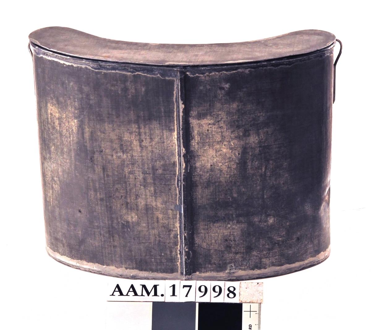 Melkebeholder, fra krigen 1940-45.  Blikk, fortinnet.  Smal, høy, buet beholder til melk,  beregnet på å feste med  stropp av tøy rundt halsen og holdt fast  under sidebena med et belte, under klærne.  Laget av ett stykke, med en skjøt midt på  yttersiden. En liten hank i hvert side,  flatt lokk til å sette ned i.