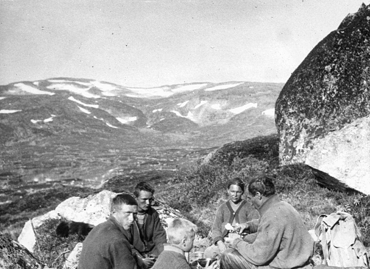 Bildet er fra Kalvvatn-området sør i Nordland. Nistepause. En gruppe samer sitter i ring og spiser. I bakgrunnen ser vi fjellandskap med snøflekker. Det er sommer og sola skinner.
