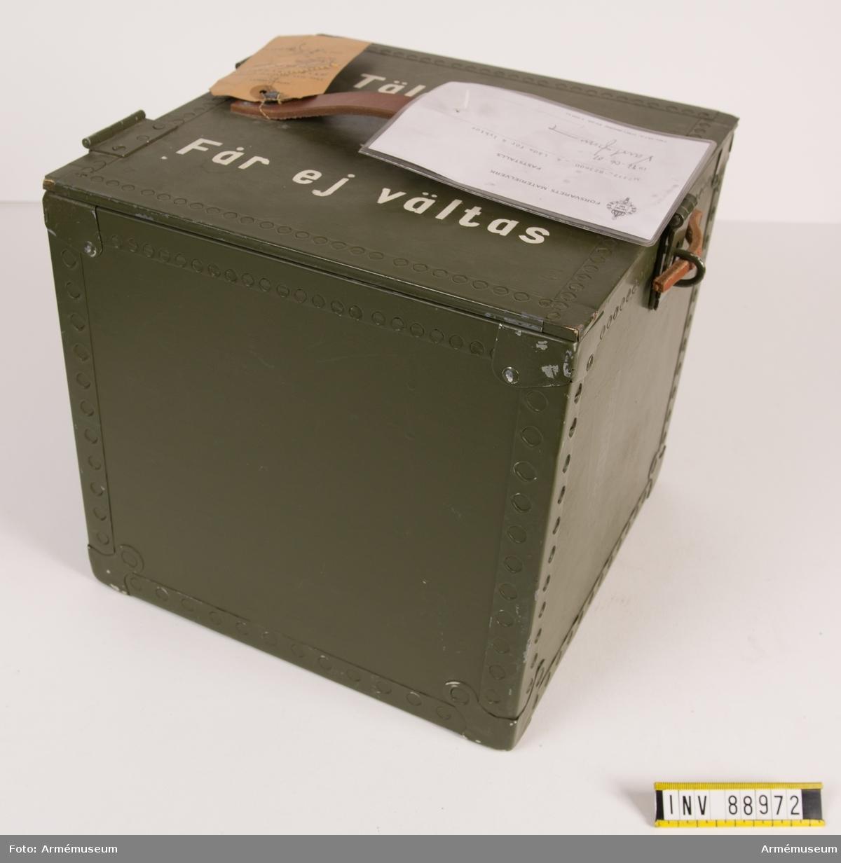 """Låda med 4 fack för tältlyktor. Bärhandtag av läder på lockets ovansida, lås och beslag av järn. Märkt på ovansidan: Tältlyktor, får ej vältas. Vidhängande modellapp med text: """"Försvarets materielverk. Fastställs. M 7332-823600-4 Låda för 4 lyktor 1986-06-01. (oläslig underskrift)."""""""