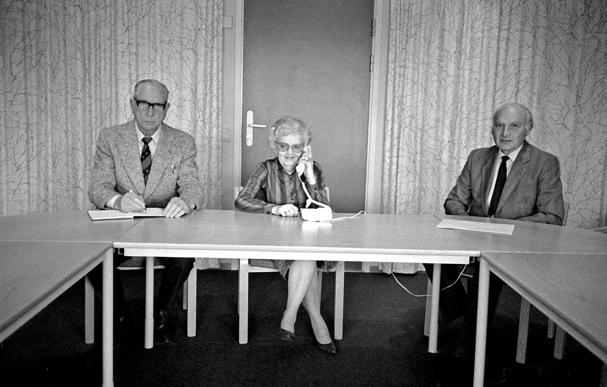To menn og en kvinne sittende ved bord.