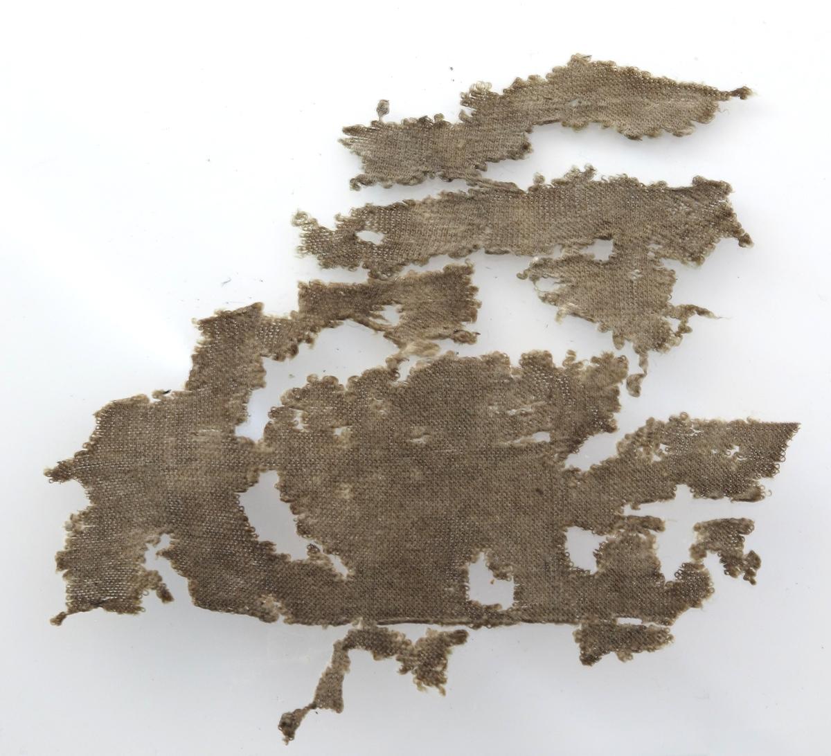 Rest av silkestrømpe. Små rester av en strikket (maskinstrikket) silkestrømpe,  engelsk ? Tilstand: nå lyst brunt på farge, forrevet stykke. Glattstrikket på den ene side, vrangen er  montert fra glasset.
