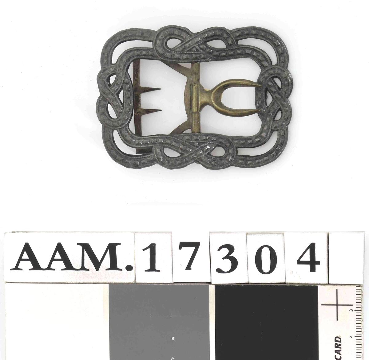 Skospenne, i stål, med hekte av messing. Formet som 2 slyngende bånd  med opphøyde knopper  i kringleform midt på hver side.    Fra  mannssko, svart,