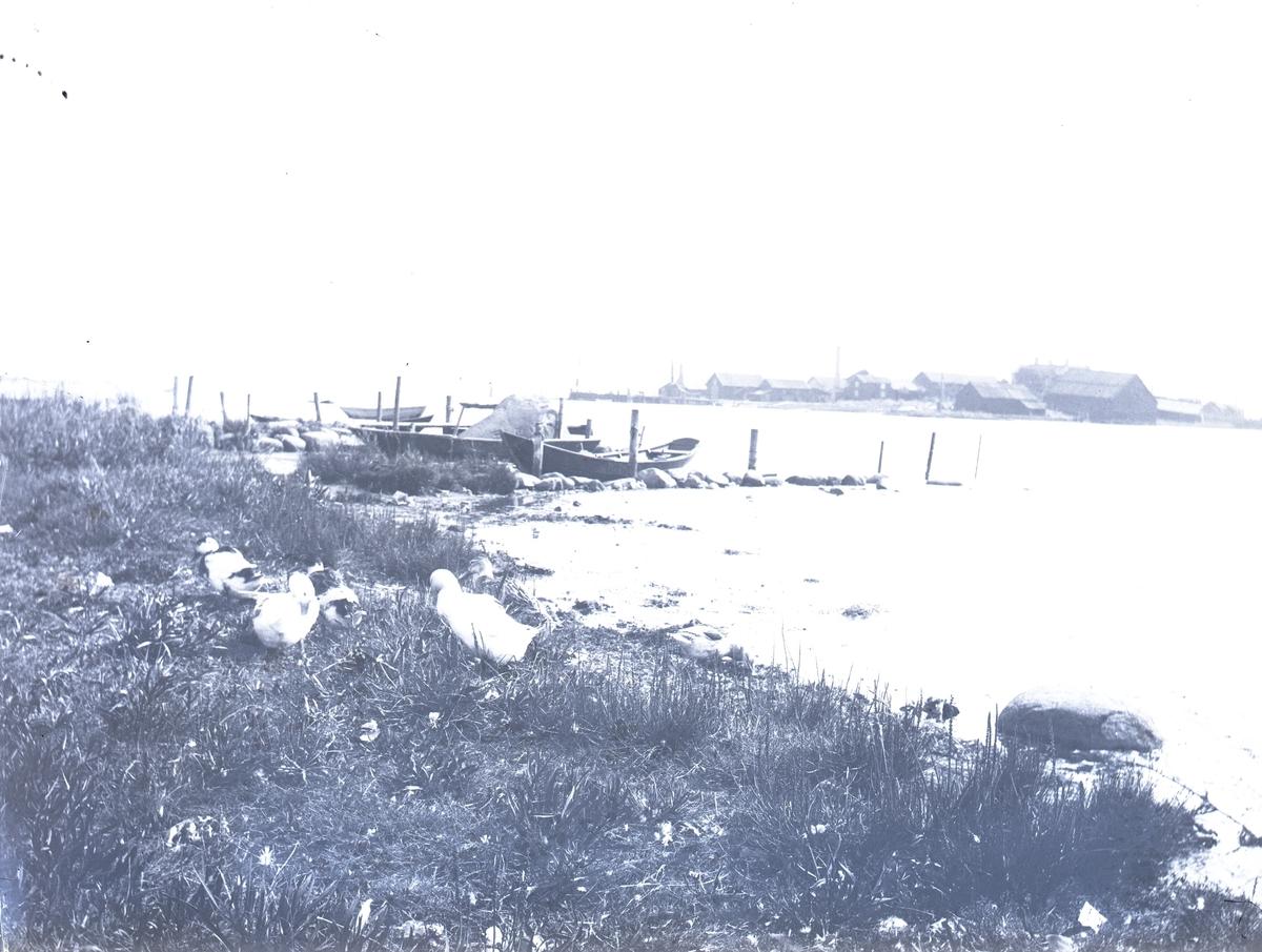 Vy med båtar, vågbrytare av stenar och Varvsholmen i bakgrund. Utsikt från Ängö mot Varvsholmen.