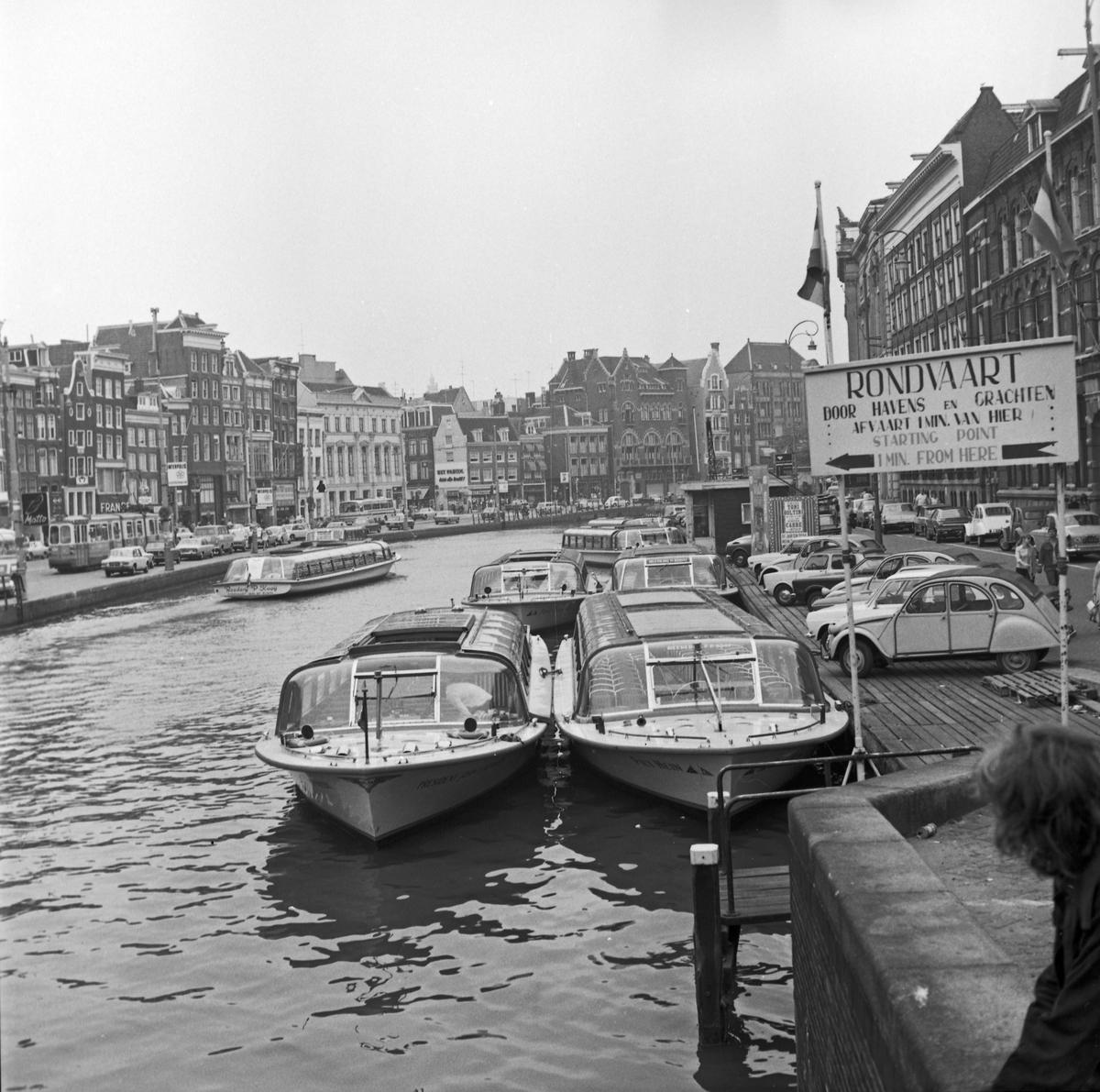 Sentrumsgater og kanaler i Amsterdam. Kanalbåter side om side med biler.