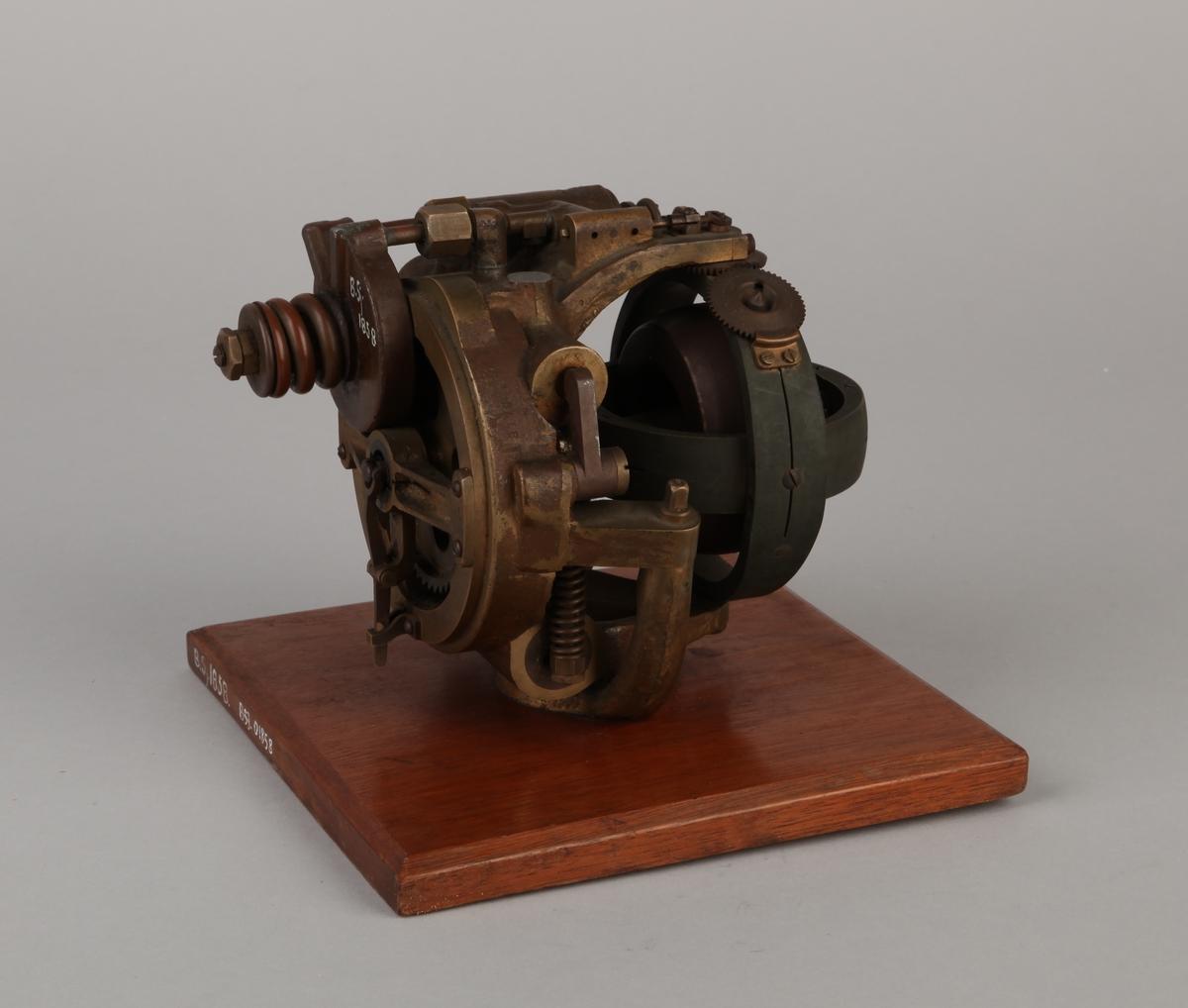 Styreinnretning bestående av tannhjul, runde metalldeler, hjullager mm.  montert på treplate. Fra krigen 1939-1945.
