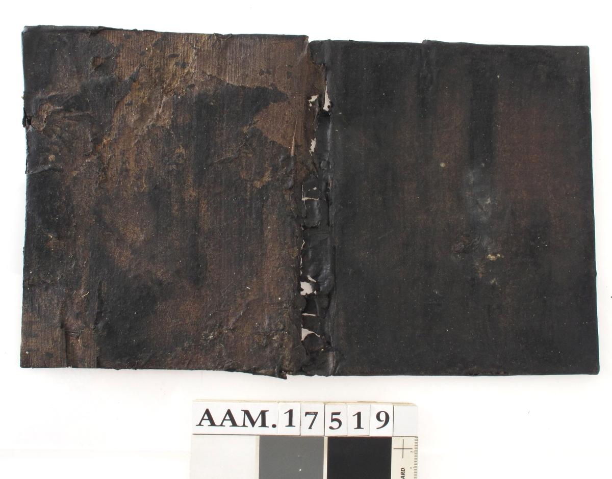 Perm til bønnebok, tynn treplate, trukket med tynt skinn. Mørkebrun, noe skinn mangler. Montert på plexiglassplate.