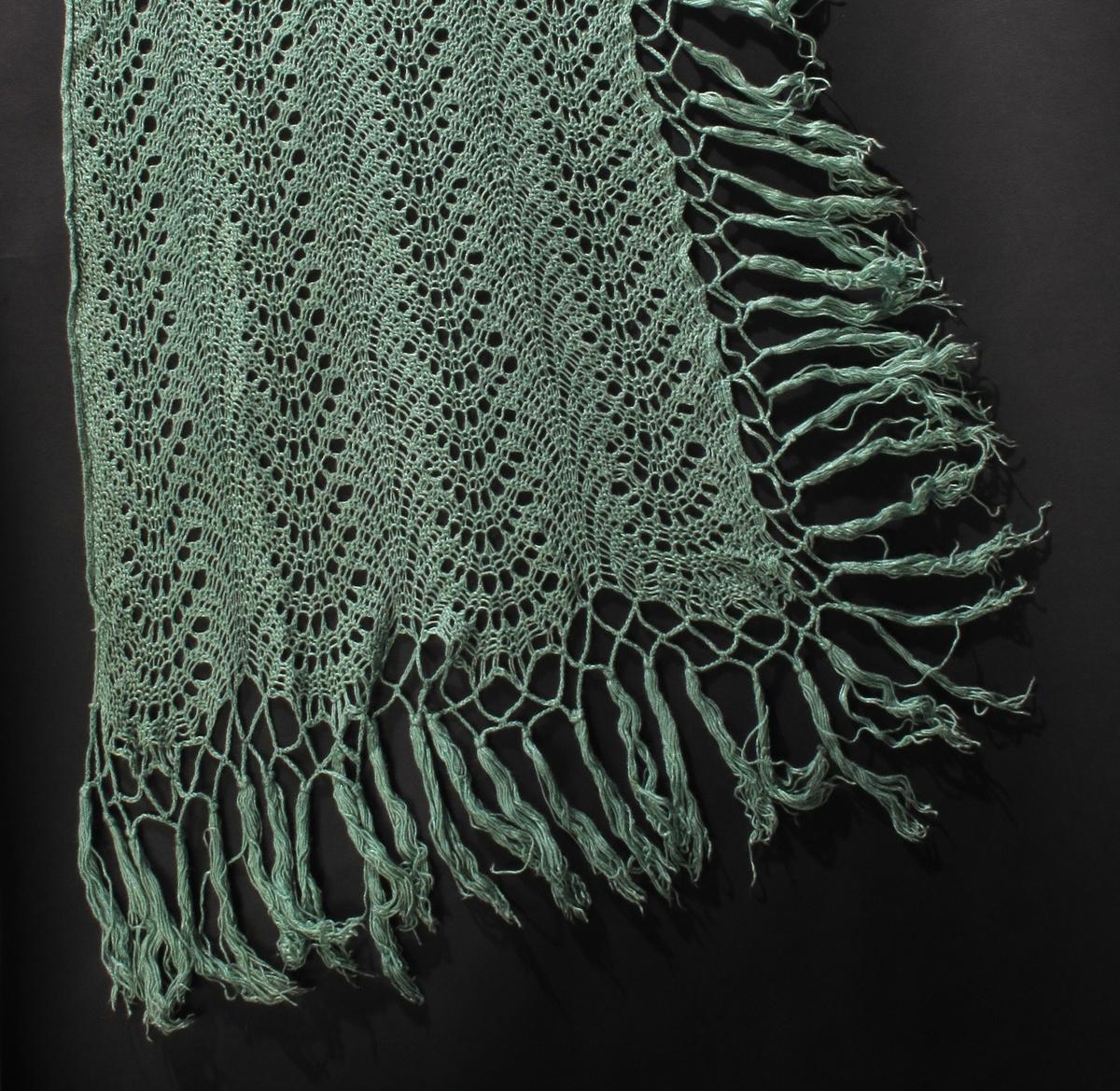 Sjal i lys grønn ull (?), Løst og tøyelig . Frynser.