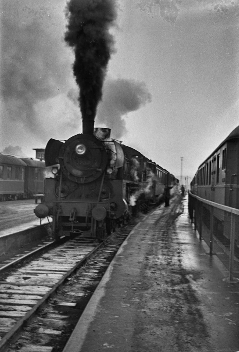 Persontog på Trondheim stasjon. Toget trekkes av damplokomotiv type 26c nr. 399.