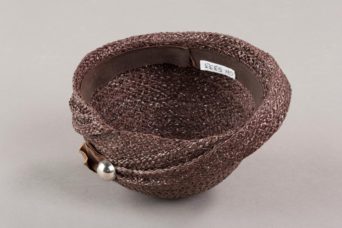 Form: Sirkelformet, avrundet  med brem og lita silkesløyfe med knapp. Bomullsbånd innvendig Brem oppbrettet i spiralform med bredde økende til avslutning hvor den er festet til pullen med en plastknapp og sløyfe