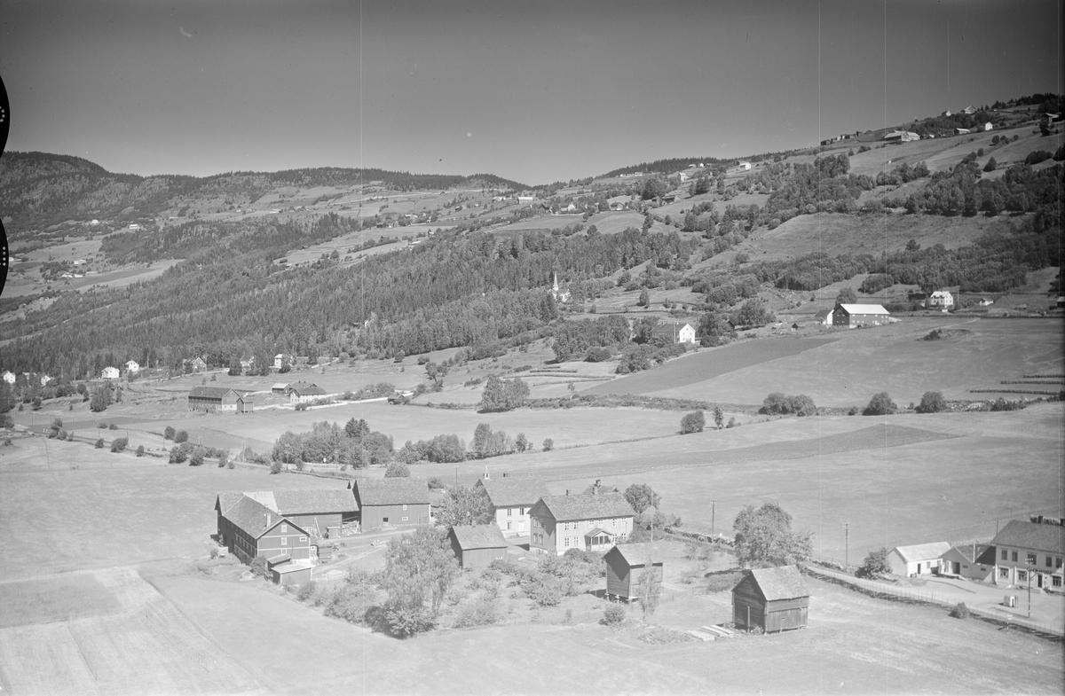 Ukjent gård, Øyer, li med flere gårder, butikk nede til høyre i bildet, kirke midt i bildet, jordbruk, slåttonn, hesjing, blandingsskog