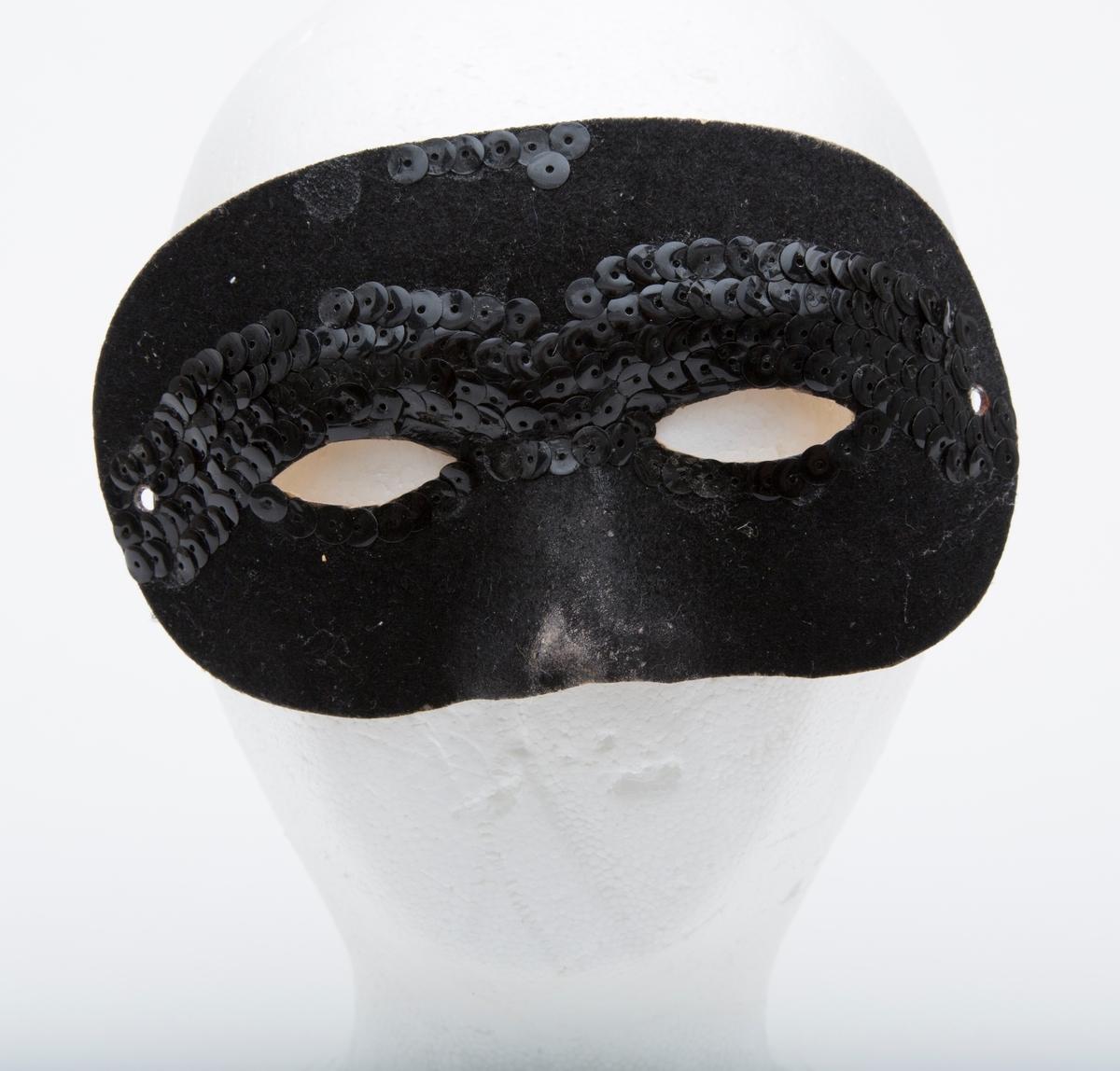 Liten karnevalsmaske med festesnor. Delvis dekket med sorte paljetter.