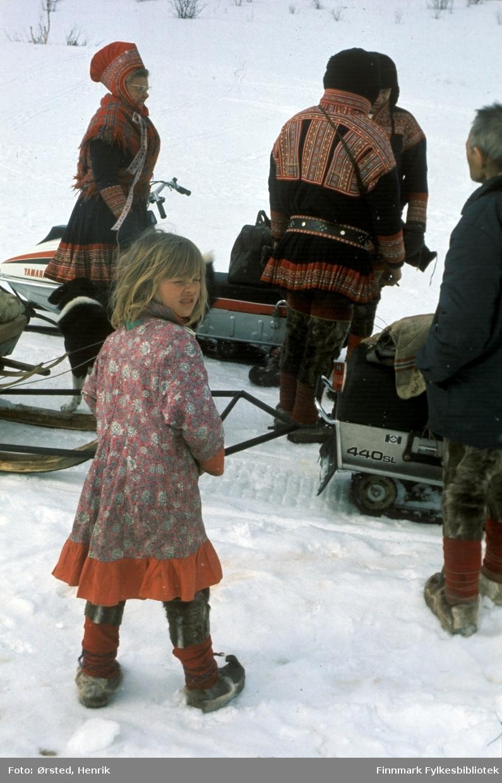 """Postfører Mathis Mathisen Buljo, bedre kjent som """"Post-Mathis"""" i samiske kretser, har ankommet et av sine stopp på postruta over Finnmarksvidda. Mathis med ryggen til i kofte.  Fotograf Henrik Ørsteds bilder er tatt langs den 30 mil lange postruta som strakk seg fra Mieronjavre poståpneri til Náhpolsáiva, videre til Bavtajohka, innover til øvre Anárjohka nasjonalpark som grenser til Finland – og ruta dekket nærmere 30 reindriftsenheter. Ørsted fulgte «Post-Mathis», Mathis Mathisen Buljo som dekket et imponerende område med omtrent 30.000 dyr og reingjetere som stadig var ute i terrenget og i forflytning. Dette var landets lengste postrute og postlevering under krevende vær- og føreforhold var beregnet til 2 dager. Bildene gir et unikt innblikk i samisk reindriftskultur på 1970-tallet. Fotograf Henrik Ørsted har donert ca. 1800 negativer og lysbilder til Finnmark Fylkesbibliotek i 2010."""
