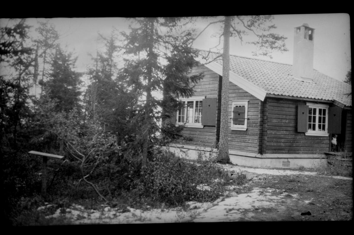 Hytte i hage med snøflekker. Et barn titter ut i døråpningen. Antagelig Villa Knyggen i Voksenlia, Oslo. Fotografert ca. 1920.