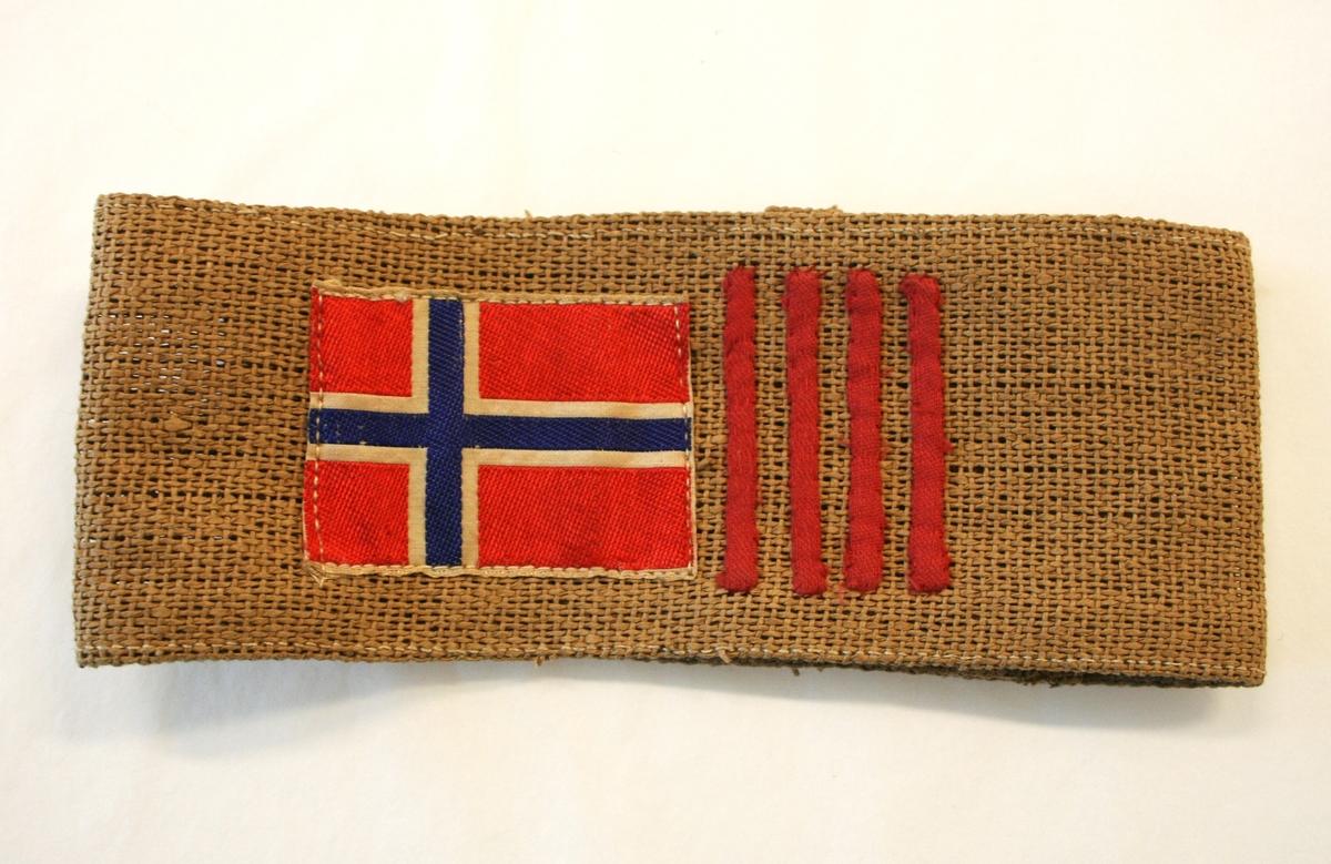Armbindet har det norske flagget etterfulgt av fire vertikale røde striper.