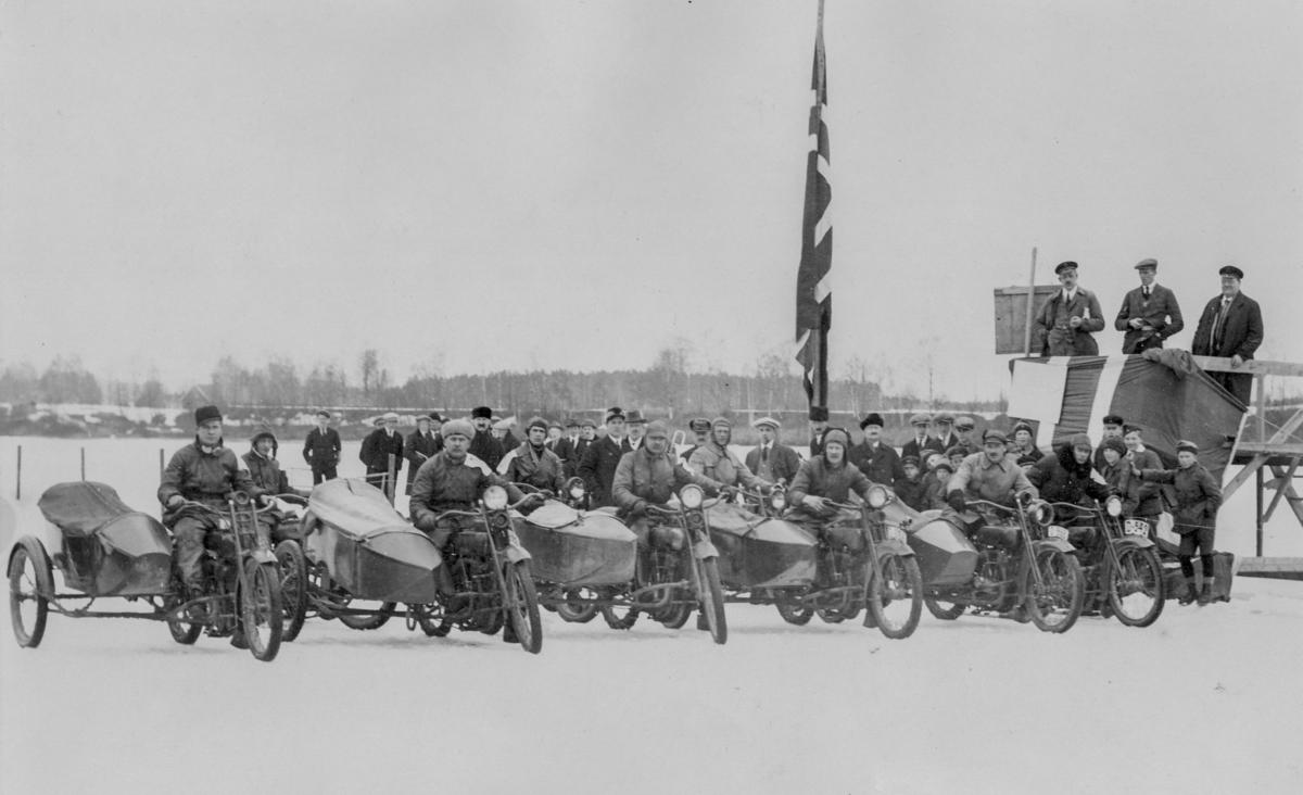 Dette bildet er fra et motorsykkelstevne på Glomma-isen ved Skarnes 28. mars 1926. I forreste rekke fra venstre: Jacob Tveter, Martin Lilleseth, Gudbrand Lukerstuen, A. Vold, Haldor Morken og Erling Morterud. Nummer to til venstre for flagget i andre rekke er Ole Rudsjordet. Reidar Løfsgaard står i midten på dommertribunen. Ukjent fotograf.