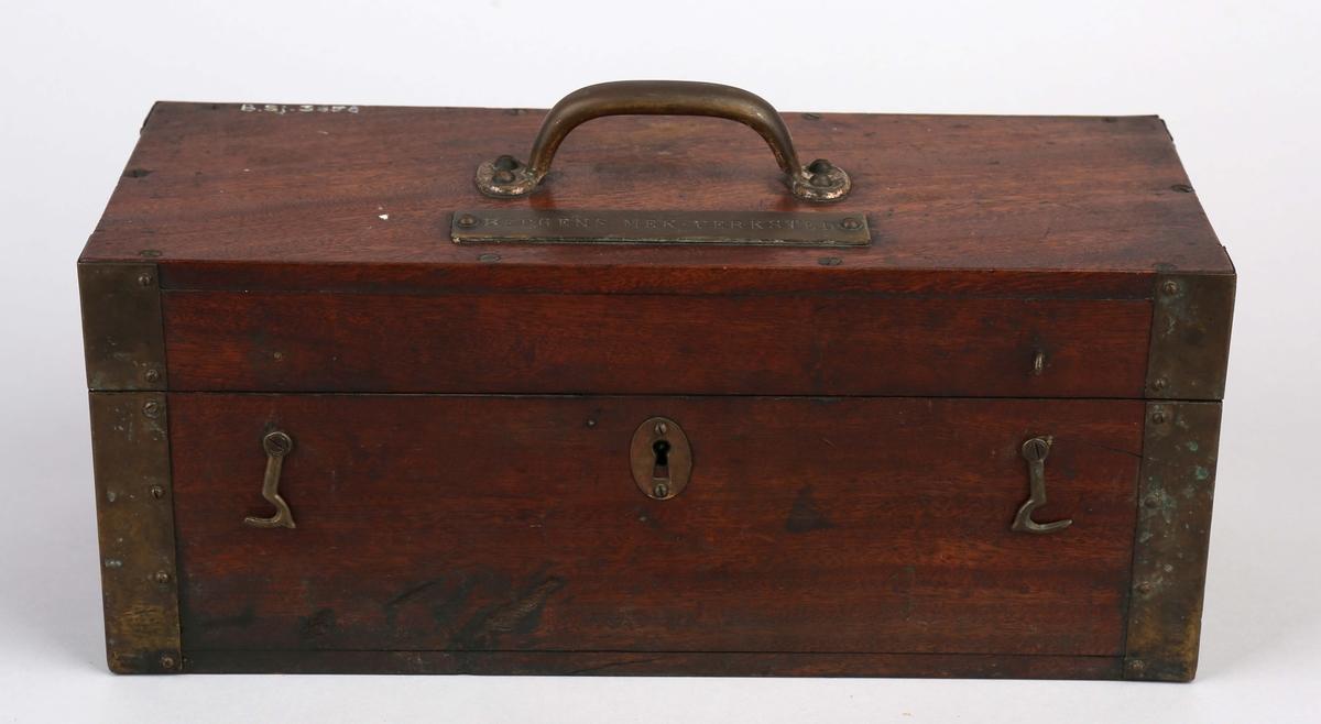 Trekasse med lokk til oppbevaring av telleapparat. Kasse beslått med messing i hjørner samt messinghåndtak og skilt på lokk.
