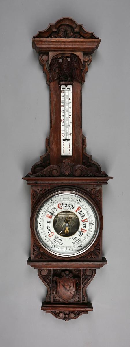 Aneroidbarometer på utskåret trepanel dekorert med ørn.