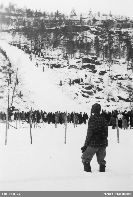 Kjell F. Hoel ser på hopprenn i Alta.  Olaf Hoel (1903-1970) var den første rektoren ved fylkets første gymnas Finnmark off. Gymnas i Alta i årene 1948-1952. Kjell F. Hoel har gitt en liten bildesamling etter sin far fra hans tid i Alta til Finnmark fylkesbibliotek. Olaf Hoel gjorde en pionerinnsats for skolen under gjenreisningen av landsdelen etter krigen.