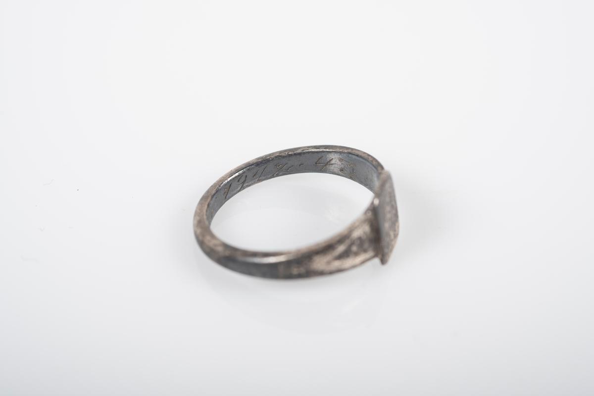 """Liten rund ring med et firkantet monogram foran med initialene BL inngravert. På innsiden er det inngravert """"Fra Far Grini 1942-43""""."""