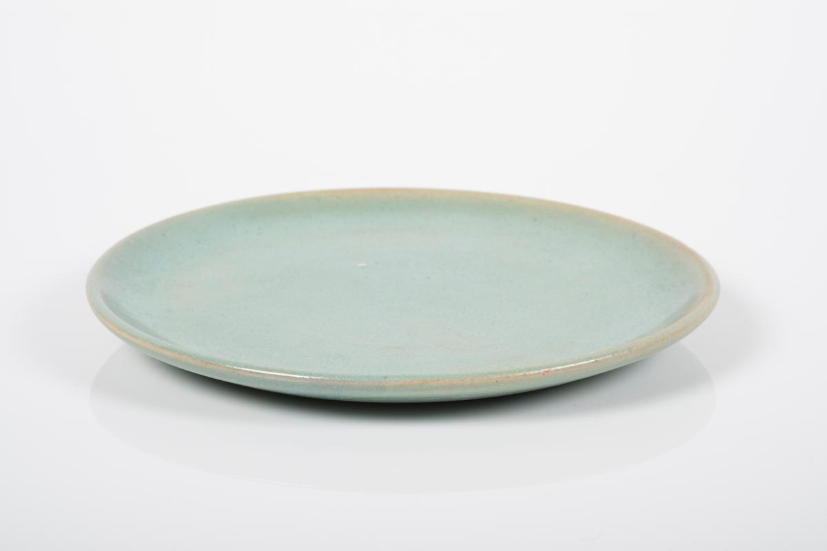 Asjett i keramikk med grønn lasur. Oversiden har blank overflate, undersiden har matt overflate. 4 små knotter på bunnen, usikker funksjon.