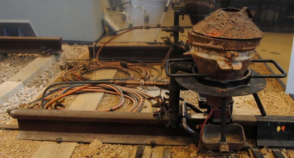 Utrustning för Thermitsvetsning från 1960-talet. Hållare för degel och brännare. Från brännarhållaren går det ut två armar som håller fast formhållarplåtarna (Jvm 50074:4-5). För att fixera formhållarplåtarna, med tillhörande formar (Jvm 50074:6-7), vrides ett handtag med en skruv åt vid var arm. På hållaren sitter ett handtag med en skruv för att reglera degelhöjd och ett handtag med en skruv för att reglera brännarhöjd. Ovanpå brännarhållaren sitter en klaff som fälles över brännaren och låses fast med en vingmutter för att fixera brännaren i brännarhållaren. Hållaren är svart, bortsett från armarna som håller fast formhållarplåtarna, och har en gul och orange markering från f.d. Banskolan. Hållaren klämmes fast runt rälshuvudet med ett handtag med en fjäderanordning och ett handtag med en skruv.
