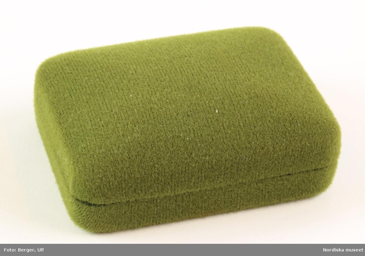 """Ett rektangulärt etui av metall, med rundade kanter och rundad överdel. Hela utsidan är täckt av grönt tyg. Etuiet öppnas med gångjärn som är övertäckta på insidan av ett vitt glansigt tyg. Samma tyg täcker insidan av locket, där det också står """"Med vänlig Luxushälsning ICA ROSTERI AKTIEBOLAG"""" i guldfärgade bokstäver. I etuiet insats av papp täckt av samma gröna tyg som på utsidan. I en sänka som går vertikalt över mitten av underdelens insida sitter två resårband som manschettknapparna (NM.332846) ska sitta i. /Elise Wargentin 2017-11"""