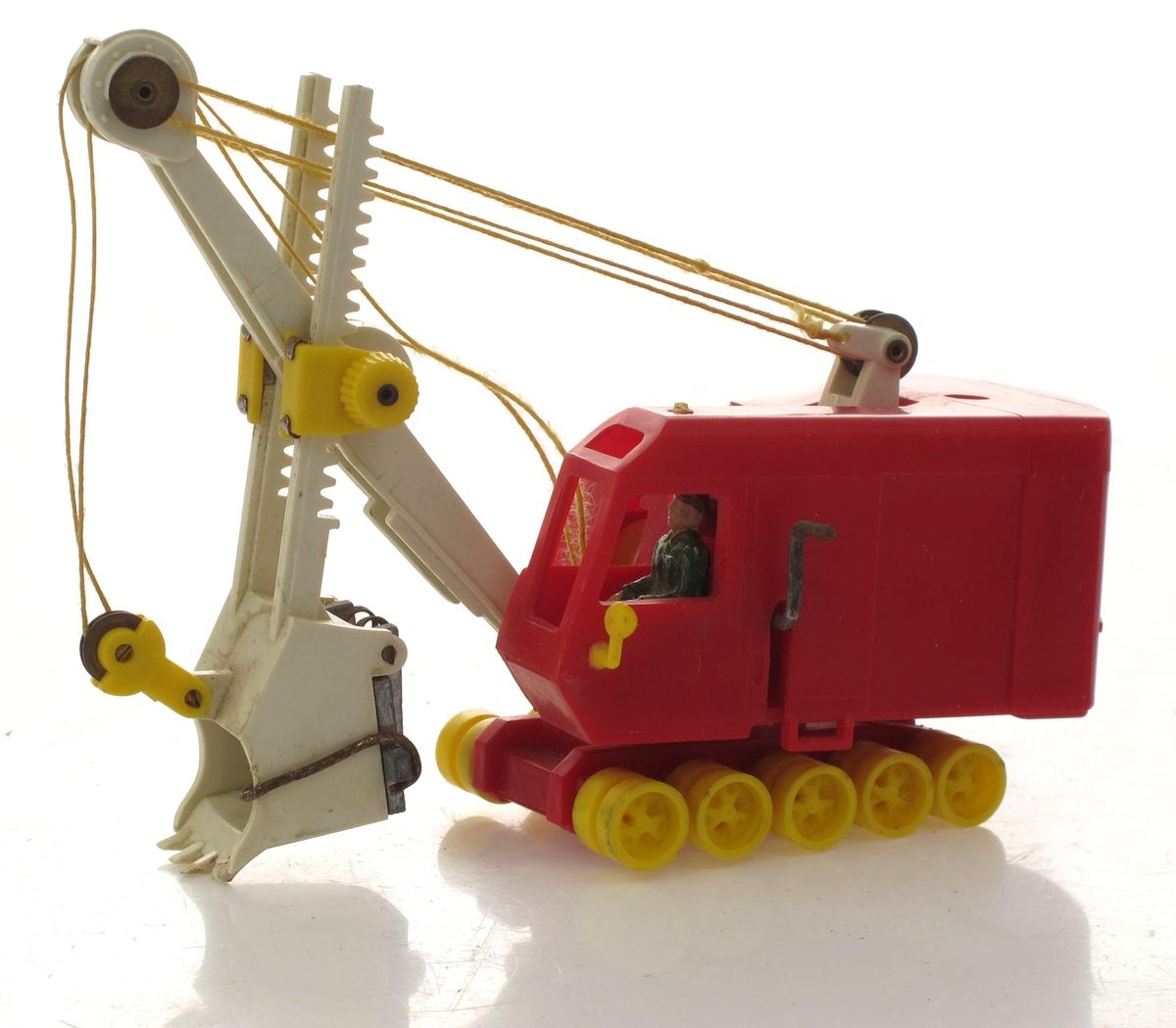 Lekegravemaskin med deler støpt i plast. Mekanisk leketøy ed bevegelige deler, snorer og sveiver, og hjul.