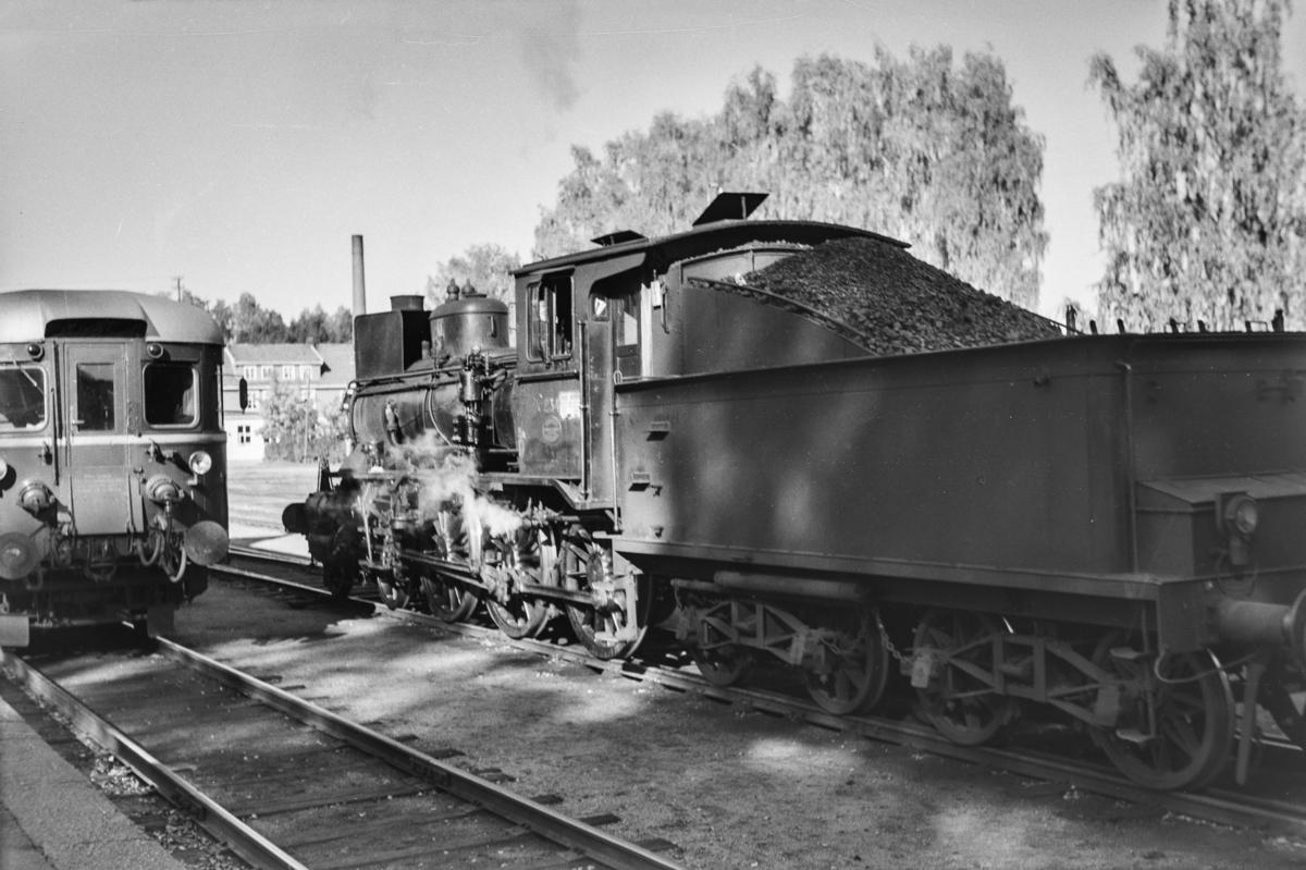 Kryssing mellom godstog og persontog på Flisa stasjon. Godstoget trekkes av damplokomotiv type 27a nr. 234.