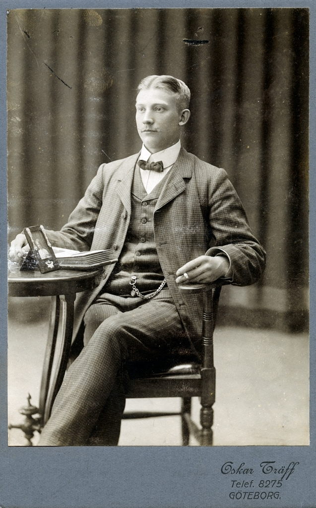 Ateljéporträtt av Oskar Träff. oskar sitter i en stol vid ett litet bord på vilket det ligger ett fotoalbum och står ett inramat fotografi med ett kvinnoporträtt. Oskar har högra handen vilandes i albumet och i vänstra handen håller han en cigarett.