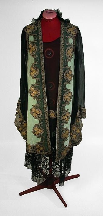 Svart rak klänning utan ärm. Rund halsringning. Livet i svart silkesvoilé, kjolen av tyll med påsydd 450 mm bred spets (mönstrad). Sömmen täcks på framsidan av broderier i läggsöm med guld- och silvertrådar. Mått: Kjolvåd 110 cm, livlängd 63 cm, kjolvåd 110 cm. Grön rak 3/4 lång sammetskappa med långa ärmar av svart silkes voile. Svart tyllrysch kring halsringningen bak. Runt kappans och ärmens kanter, guld och silver-broderier på svart voile. Mått: Hel längd 105 cm, ärmlängd 48 cm.