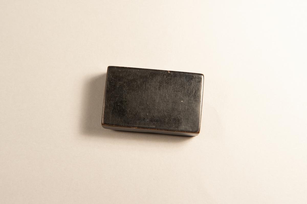 En brunsvart, rektangulär dosa med inläggningar av enkla tennband på locket.Jfr JM 20 150.