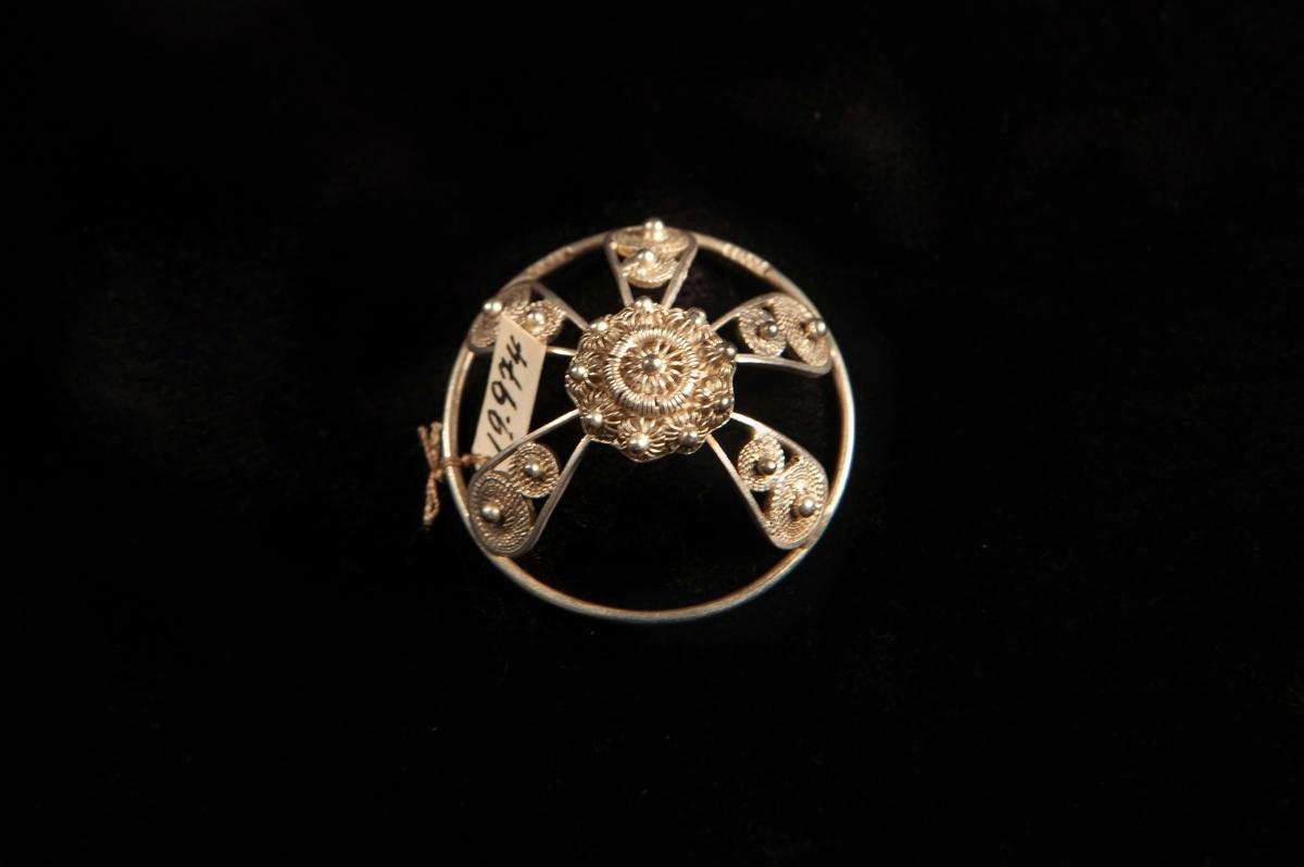 En rund malja av silver med filigranarbete, bestående av bågar upp mot en central blomma i filigran.